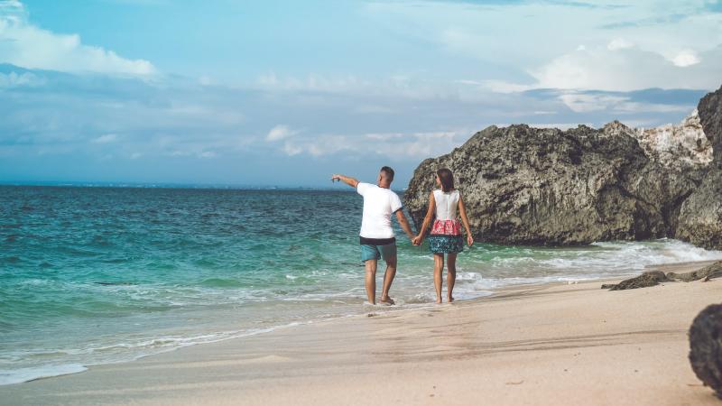 a couple walking beside body of water