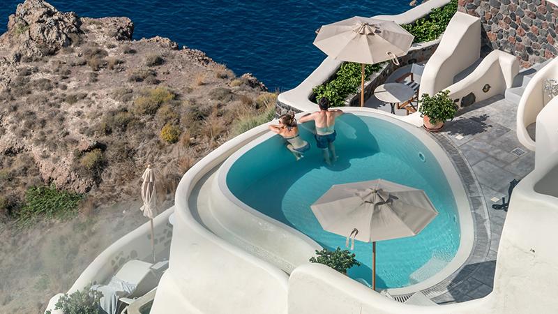 a couple at a pool, Santorini, Greece